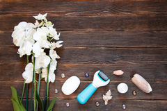 Pemza to clean up old leather heels. Pedicure care set - machine. Soap, orchids, shells, cream with a dark wooden background. spa concept Royalty Free Stock Image
