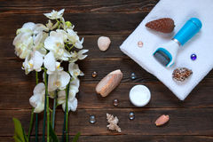 Pemza to clean up old leather heels. Pedicure care set - machine. Soap, orchids, shells, cream, white towel with a dark wooden background. spa concept Stock Photography
