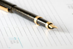 The pen. With a gold stylus lays on weekly Stock Image