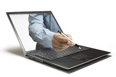 A Pen. A Hand reaches out of a computer Stock Photo