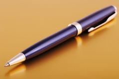 Ballpoint pen on gold background. Ballpoint pen lying on shiny gold surface with reflections and selective focus on the ball point Royalty Free Stock Photos