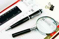Pen and Agenda with a tools of punctuality. Pen and Agenda with a various tools of punctuality stock photo