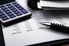 Pen on background of calculator and accounting papers. Large pen on background of calculator and accounting papers stock photo