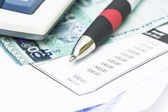 Pen on bank statement and bank notes Stock Photos