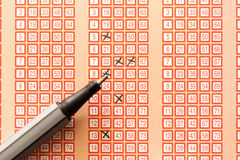 Pen and bingo lotto lottery ticket with crossed numbers Royalty Free Stock Photos