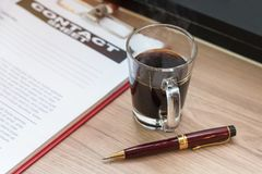 Pen,black coffee,business document and contact sheet royalty free stock photo