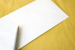 Pen on blank envelope. Yellow pen on blank envelope on yellow background Royalty Free Stock Image