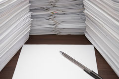 Pen and blank paper. Besides piles of documents Stock Photos