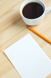 Pen, blank paper on board and cup of coffe Stock Images