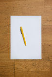 Pen on a blank paper sheet on a wooden table Stock Photography