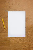 Pen and blank paper sheet on a wooden table. Pen and a blank white paper sheet on a worn wooden table surface, viewed from above stock photo