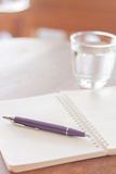 Pen and blank spiral notebook on wooden table Stock Photos