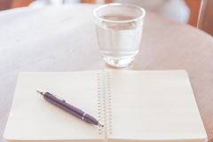 Pen and blank spiral notebook on wooden table Stock Photography