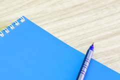 Pen blue and Blank blue book empty cover book spiral stationery school supplies. For education business idea book cover design note pad memo on wooden Royalty Free Stock Photo