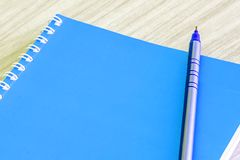 Pen blue and Blank blue book empty cover book spiral stationery school supplies. For education business idea book cover design note pad memo on wooden Royalty Free Stock Photography