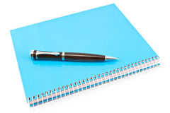Pen on blue spiral notebook. On white Stock Image