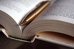 Pen and Book. A gold ballpoint pen on an open book stock images
