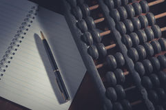 Pen on book with abacus,vintage filtered. Stock Image