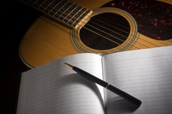 Pen and book on acoustic guitar. Royalty Free Stock Photos