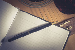 Pen and book on acoustic guitar Stock Photography