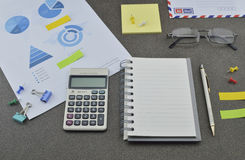 Pen, book, calculator, glasses and financial chart and graph Stock Photos