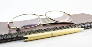 Pen, book and spectacles. On white background Stock Image
