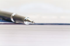 Pen and book on white Royalty Free Stock Photography