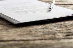 Pen bovenop stuk van document op klembord stock foto