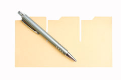 Pen and brown paper. On white Royalty Free Stock Images