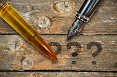 Pen and bullet. Fountain pen and bullet on wooden background and three question marks Stock Photos
