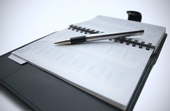 Pen on business day planner. Closeup of a business day planner with a pen stock image
