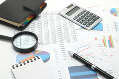 Pen, business items, and business documents with numbers and charts. Stock Image