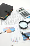 Pen, business items, and business documents with numbers and charts. Royalty Free Stock Photos