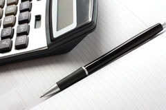 Pen and calculator. Pen and a calculator lying on the diary Stock Images