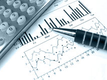 Pen and calculator against the graph (in blue) Stock Photo