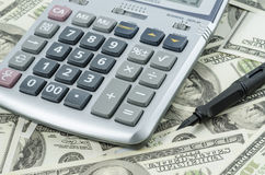 Pen and Calculator on a background of american dollar bills. Stock Photo
