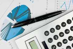Pen and calculator on a background of diagrams Royalty Free Stock Photography