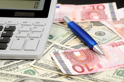 Pen, calculator on banknotes Stock Image