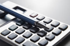 Pen and calculator on business paper. Royalty Free Stock Photos