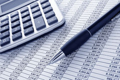 Pen and Calculator on Cash Financial Spreadsheet royalty free stock photography