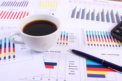 Pen, calculator and cup of coffee on financial graph, business concept Royalty Free Stock Images