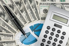 Pen,calculator and dollars on chart closeup Royalty Free Stock Images