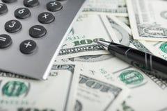 Pen,calculator and dollars  closeup. Royalty Free Stock Image