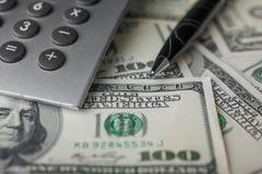 Pen,calculator and dollars  closeup Stock Images