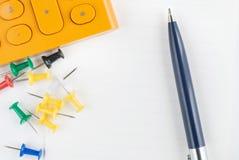 Pen, calculator en punaise op het document Stock Fotografie