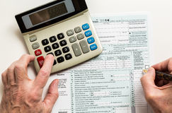Pen and calculator on 2014 form 1040 Royalty Free Stock Image