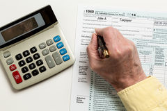 Pen and calculator on 2014 form 1040 Stock Photos