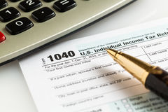 Pen and calculator on 2014 form 1040 Stock Images