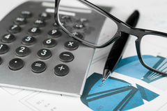 Pen, calculator and glasses on a background of diagrams Stock Photography