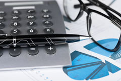 Pen, calculator and glasses on a background of diagrams. Stock Photos